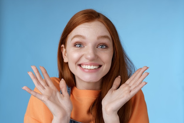 Gelukkig verheugend emotioneel jong glimlachend roodharig meisje blauwe ogen krijgen opwindend nieuws grijnzend juichen gelukkig opgeheven handen opgewonden grote ogen verrast geaccepteerd beroemde universiteit, blauwe achtergrond