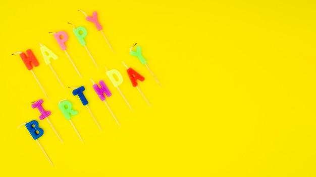 Gelukkig verjaardagsbericht met kleurrijke kaarsen en exemplaarruimte