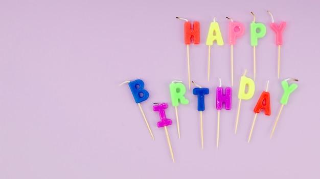 Gelukkig verjaardagsbericht met kleurrijke kaarsen op purleachtergrond