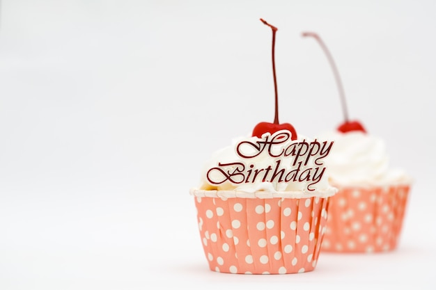 Gelukkig verjaardagswoord en kopcake met rode kers
