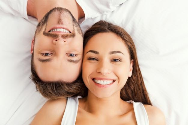Gelukkig verliefde paar. bovenaanzicht van mooie jonge verliefde paar samen in bed liggen en glimlachen