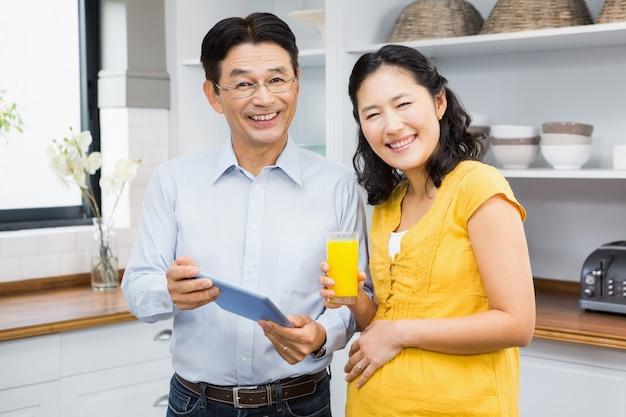 Gelukkig verwachtend paar die tablet in de keuken gebruiken
