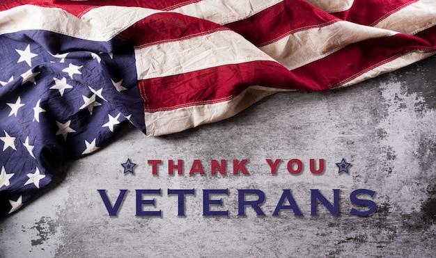 Gelukkig veteranendag concept. amerikaanse vlaggen tegen een donkere stenen achtergrond. 11 november.