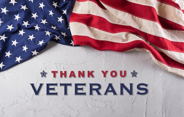 Gelukkig veteranendag concept. amerikaanse vlaggen tegen een witte stenen achtergrond. 11 november.