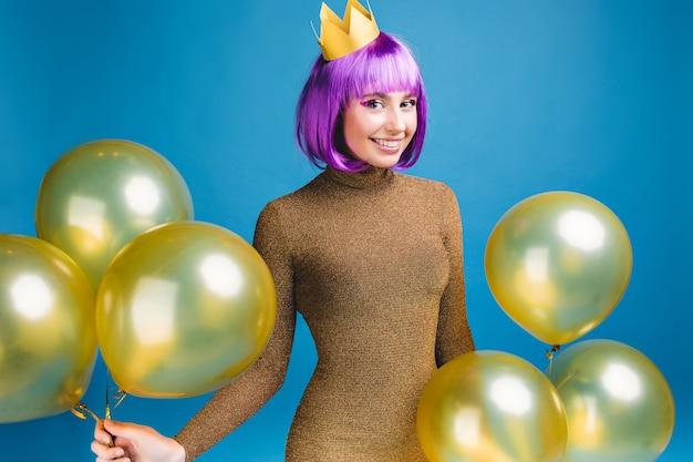 Gelukkig vieren momenten van glimlachte jonge vrouw met plezier met gouden ballonnen. luxe modieuze jurk, paars haar knippen, kroon, feest, nieuwjaarsfeest, verjaardag.