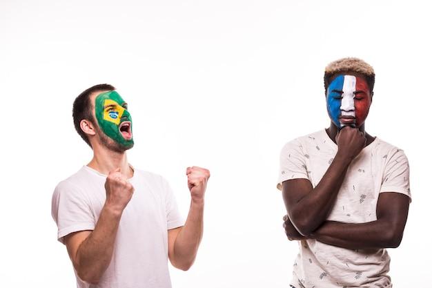 Gelukkig voetbalfan van brazilië vieren overwinning boos voetbalfan van franse nationale teams met geschilderd gezicht geïsoleerd op een witte achtergrond