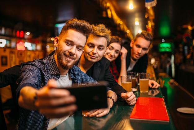 Gelukkig voetbalfans maakt selfie op telefoon aan de toog in een sportcafé, viering van de overwinning