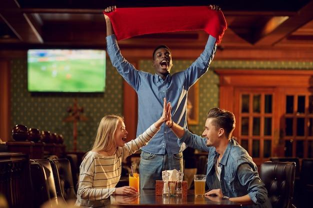 Gelukkig voetbalfans met rode sjaal en bal kijken naar tv-uitzendingen, vrienden in de bar