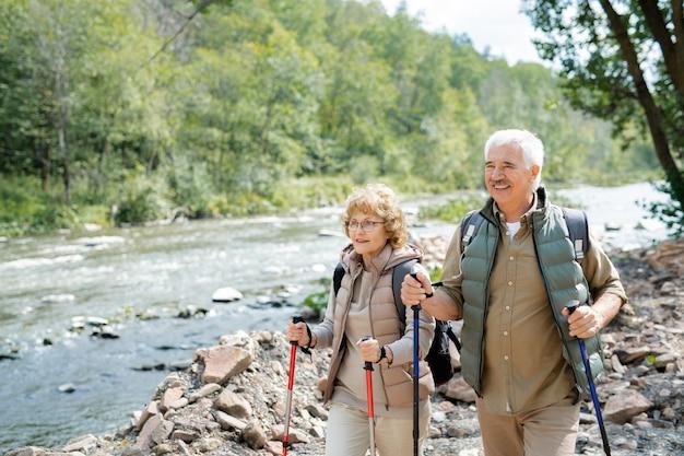 Gelukkig volwassen actieve wandelaars met rugzakken en wandelstokken die langs de rivier langs stenen lopen terwijl u geniet van de reis