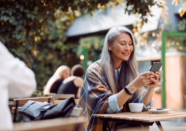 Gelukkig volwassen aziatische vrouw surft op internet op de telefoon aan een kleine tafel op het terras van een café in de openlucht