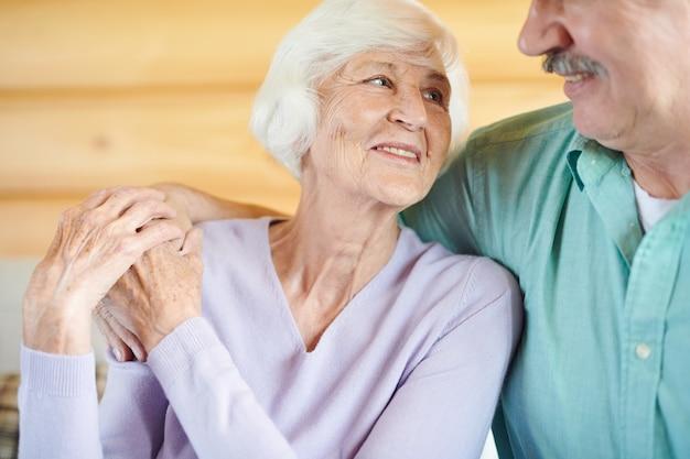Gelukkig volwassen casual echtgenoten kijken elkaar met een glimlach terwijl ze thuis samen ontspannen