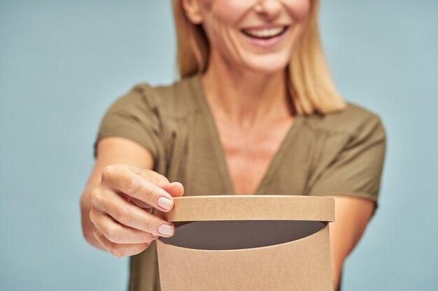 Gelukkig volwassen dame poseren met geschenkdoos geïsoleerd op blauwe achtergrond
