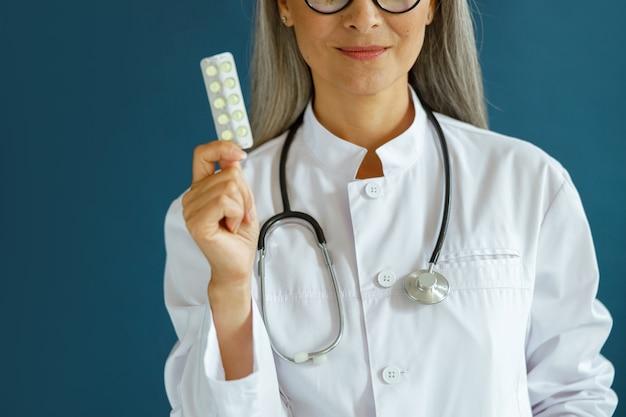 Gelukkig volwassen dame therapeut in witte jas toont pillen op blauwe achtergrond
