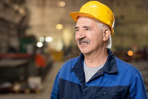 Gelukkig volwassen ingenieur of voorman in veiligheidshelm en werkkleding staande in grote industriële fabriek of fabriek