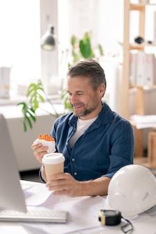 Gelukkig volwassen ingenieur zit door bureau voor computermonitor en grappige cupcake in zijn hand te kijken alvorens het te eten