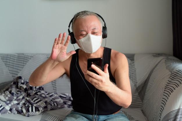 Gelukkig volwassen japanse man met masker video bellen met koptelefoon thuis onder quarantaine