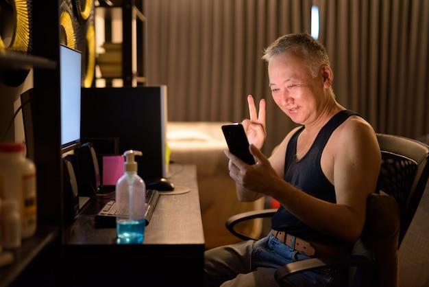 Gelukkig volwassen japanse man video-bellen met telefoon tijdens het werken vanuit huis
