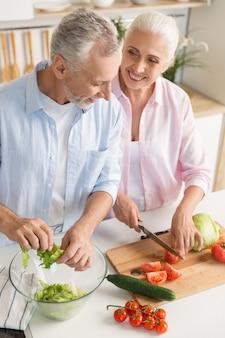 Gelukkig volwassen liefdevolle paar familie koken salade