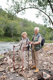 Gelukkig volwassen man en vrouw met wandelstokken die naar je kijken terwijl je op stenen langs de rivier staat