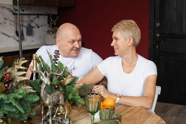Gelukkig volwassen man en vrouw zitten aan de tafel met kerstversiering en kijken naar elkaar