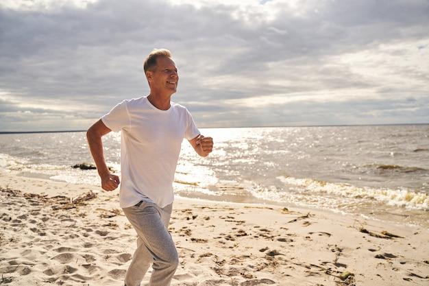 Gelukkig volwassen man geniet van cardiotraining in de open lucht door langs de kust te rennen