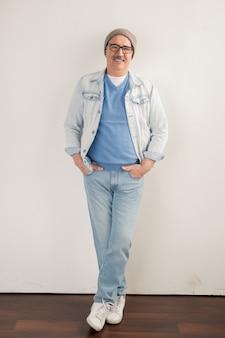 Gelukkig volwassen man in spijkerbroek, pullover, jas, muts en sneakers leunend over een witte muur terwijl hij naar jou kijkt
