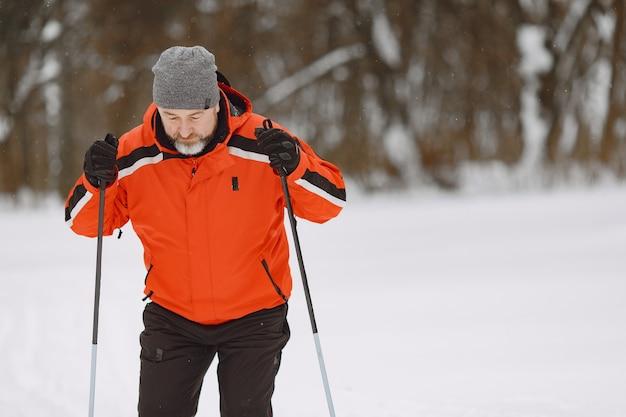 Gelukkig volwassen man in winter park. senior activewear trekking in het bos ter vrije besteding