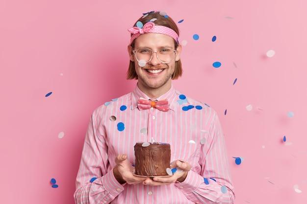 Gelukkig volwassen man viert een jaar werken in het bedrijf houdt kleine taart feliciteert de felicitatie van collega's glimlacht vreugdevol draagt hoofdband gestreept shirt en bowtie cofetti valt op hem