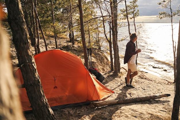 Gelukkig volwassen mannetje brengt actieve vakantie door met tent in de natuur en drinkt 's ochtends koffie