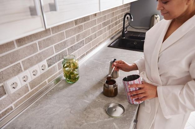 Gelukkig volwassen midden-oosterse etniciteit vrouw in wit wafel gewaad bereidt koffie in een geiser koffiezetapparaat terwijl ze in de keuken thuis
