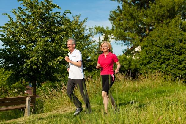 Gelukkig volwassen of hoger paar die nordic walking in de zomer doen