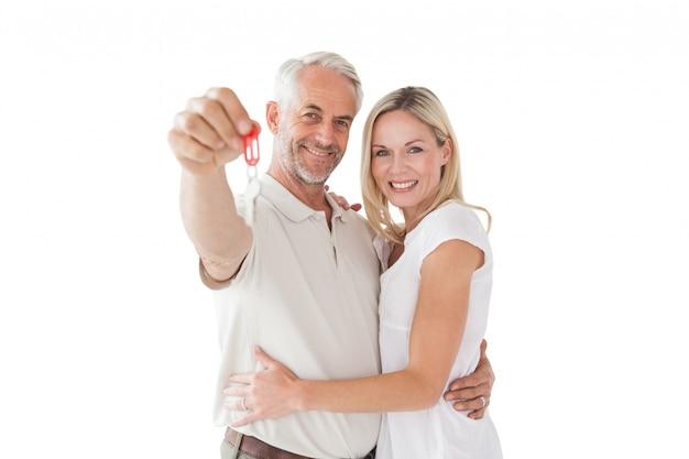 Gelukkig volwassen paar die nieuwe huissleutel houden