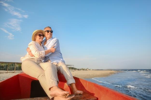 Gelukkig volwassen paar in boot in badplaats