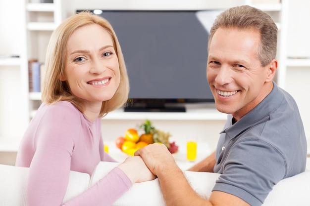 Gelukkig volwassen paar. vrolijk volwassen stel zit voor de tv en kijkt over de schouder mee