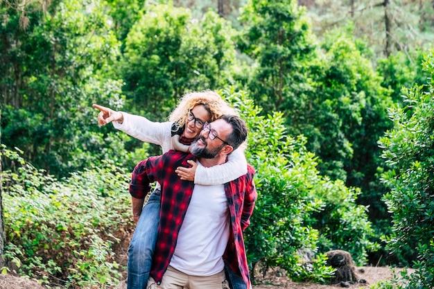Gelukkig volwassen stel geniet van de vrijetijdsactiviteiten in de natuur, samen met een man die een vrolijke, mooie vrouw draagt met een groen bos in scène