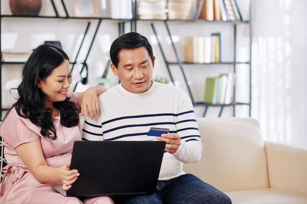 Gelukkig volwassen vietnamees koppel zittend op de bank met laptop, online aankopen doen en betalen met creditcard