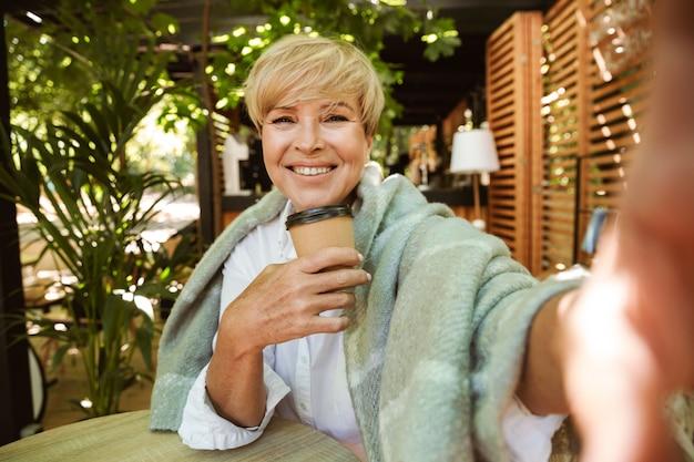 Gelukkig volwassen vrouw gewikkeld in deken nemen van een selfie