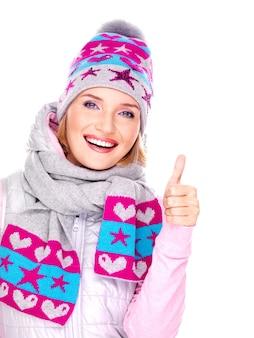 Gelukkig volwassen vrouw in winterkleren met heldere positieve emoties toont duimen omhoog teken geïsoleerd op wit
