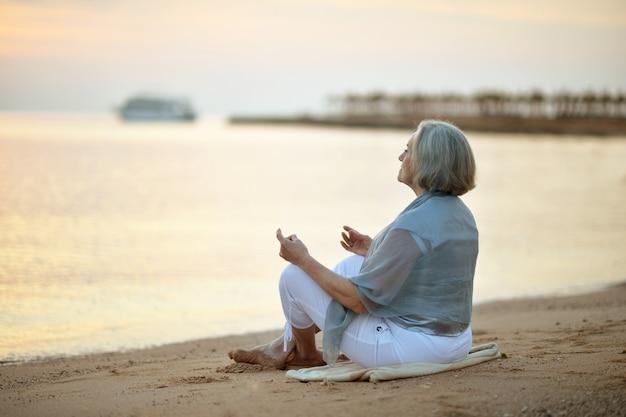 Gelukkig volwassen vrouw mediteren op een strand