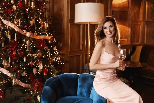 Gelukkig volwassen vrouw met brede glimlach, in een avondjurk, houdt een glas champagne en zit op een fauteuil in de buurt van de kerstboom op interieur ingericht voor nieuwjaar.