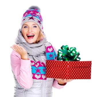 Gelukkig volwassen vrouw met een cadeau in een winter bovenkleding op wit wordt geïsoleerd