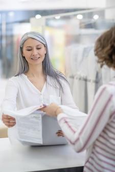 Gelukkig volwassen vrouw met lang grijs haar schone kleren nemen bij stomerij en vrouwelijke werknemer aan balie