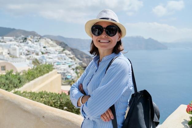 Gelukkig volwassen vrouw toerist reizen op het beroemde eiland santorini, vrouw met gekruiste armen kijken naar camera, zee hemelachtergrond