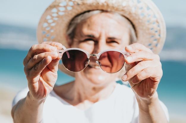 Gelukkig volwassen vrouw van 50 jaar op het strand met trendy zonnebril en een hoed