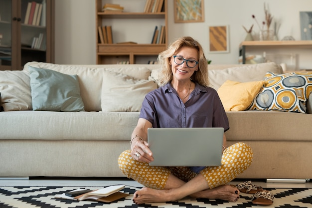 Gelukkig volwassen vrouwtje met gekruiste benen in vrijetijdskleding met laptop terwijl ze naar het display kijkt tijdens communicatie via videochat