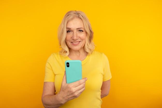 Gelukkig volwassen wijfje met blauwe mobiel op de gele achtergrond.