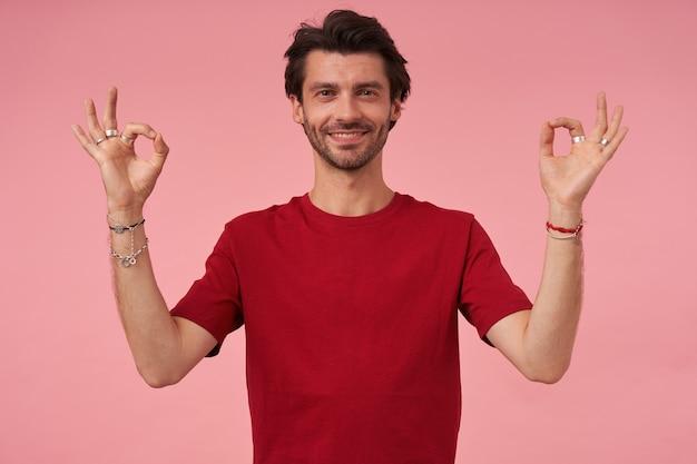 Gelukkig vreedzame jonge man met stoppels in rode t-shirt mudra teken tonen en mediteren