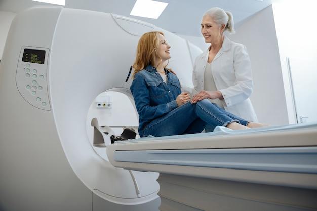 Gelukkig vreugdevolle aantrekkelijke vrouw zittend op de onderzoekstafel en kijken naar haar arts tijdens een bezoek aan een ziekenhuis