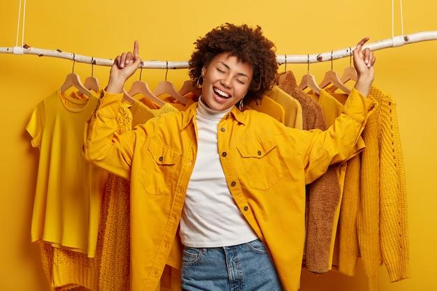 Gelukkig vreugdevolle afro-vrouw danst met triomf tegen kledingrek, geeft de voorkeur aan outfits van gele kleur, draagt een modieuze jas en spijkerbroek, beweegt actief in de buurt van de huisgarderobe.