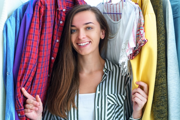 Gelukkig vreugdevolle brunette vrouw permanent in de buurt van garderoberek vol kleren op hangers, niet wetend wat te doen. niets om concept te dragen. vrouw die en kleren kiezen zoeken voor speciale gelegenheid.
